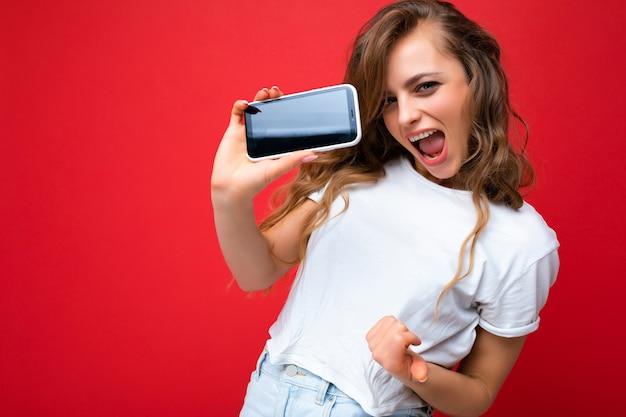 Verrückte lächelnde junge blonde frau, die gut aussieht, trägt weißes t-shirt, das isoliert auf rotem hintergrund steht, mit kopierraum, der das telefon hält, das smartphone in der hand mit leerer bildschirmanzeige für mock-up