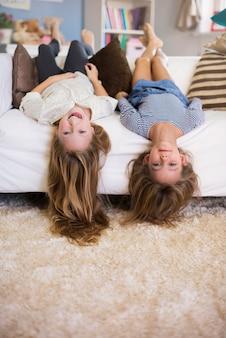 Verrückte mädchen liegen kopfüber auf dem sofa