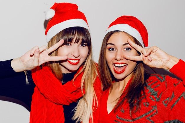 Verrückte neujahrsparty stimmung. zwei betrunkene lachende frauen, die spaß haben und in niedlichen maskeradenhüten posieren. roter pullover und schal. zeichen zeigen. weiße zähne, helles make-up.