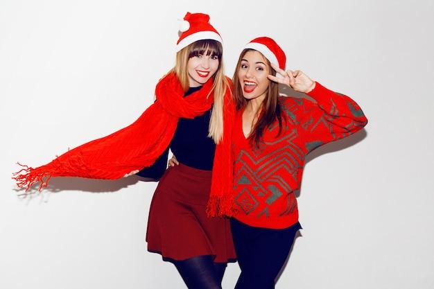 Verrückte neujahrsparty stimmung. zwei betrunkene lachende frauen, die spaß haben und in niedlichen maskeradenhüten posieren. roter pullover und schal.