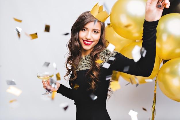 Verrückte partyzeit der schönen frau im eleganten schwarzen kleid und in der gelben krone, die neujahr, geburtstag feiern, spaß haben, tanzen, alkoholcocktails trinken. bewegungsgesicht, rote lippen, goldene luftballons.