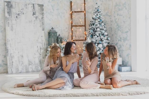 Verrückte partyzeit von vier schönen stilvollen frauen im eleganten lässigen outfit, das weihnachten feiert