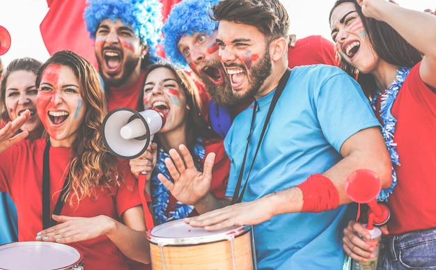 Verrückte sportfans spielen schlagzeug und schreien, während sie ihr team unterstützen