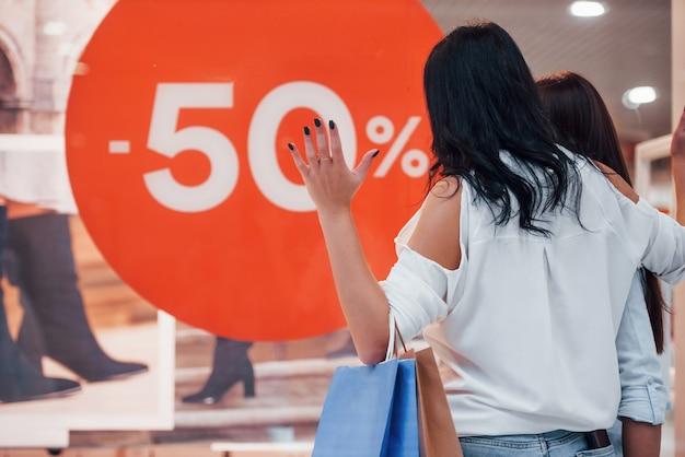 Verrückte verkäufe. zwei junge frauen verbringen gemeinsam einen einkaufstag im supermarkt.