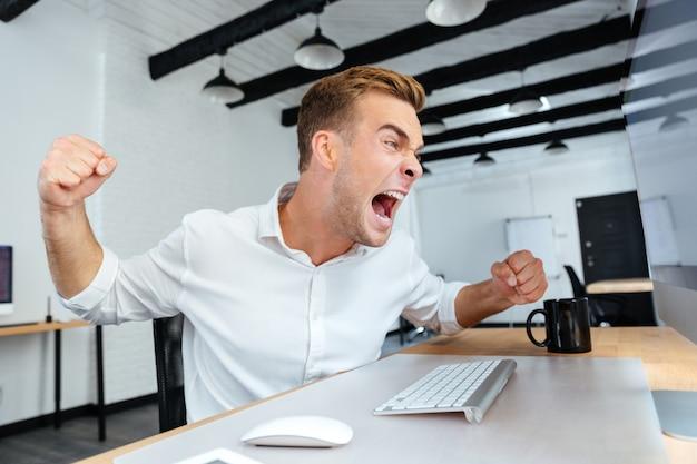 Verrückter aggressiver junger geschäftsmann, der im büro sitzt und schreit
