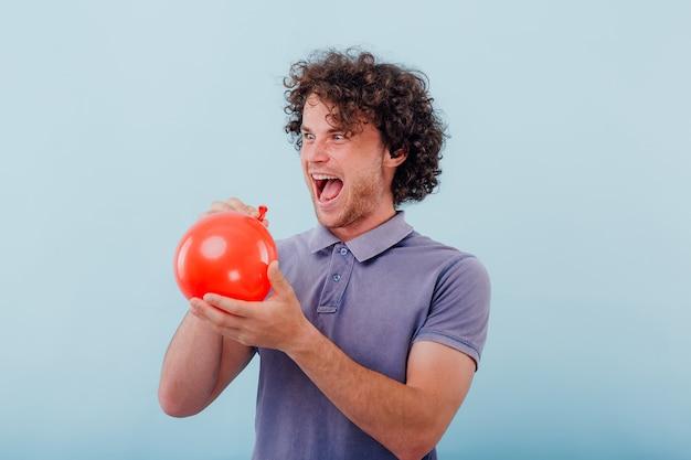 Verrückter aussehender junger mann mit lockigem haar, der halb aufgeblasenen roten ballon hält