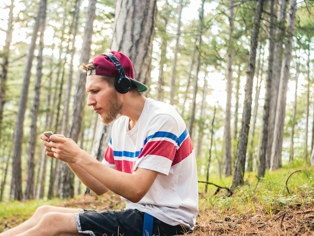 Verrückter bärtiger hippie in zufälligem und in der kappe sitzen im naturwald mit dem telefon und kopfhörern, die das spielen auf smartphone spielen