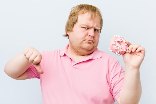 Verrückter blonder mann, der einen donuts hält