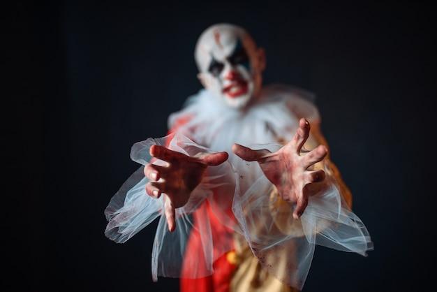 Verrückter blutiger clown, der mit den händen nach dem opfer greift, vorderansicht. mann mit make-up im karnevalskostüm, verrückter verrückter