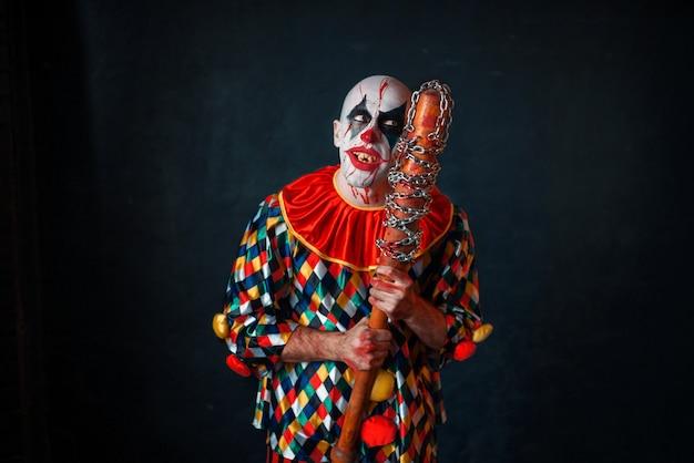 Verrückter blutiger clown mit baseballschläger. mann mit make-up im halloween-kostüm, zombie