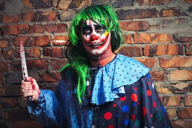 Verrückter clown mit einem messer auf einem backsteinmauerhintergrund halloween-konzept