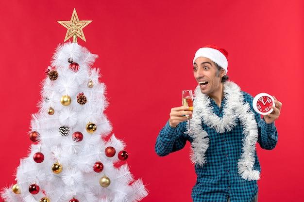 Verrückter emotionaler junger mann mit weihnachtsmannhut und hält ein glas wein und uhr