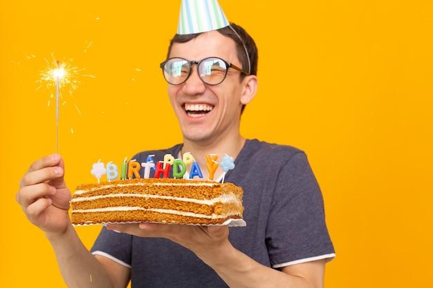 Verrückter fröhlicher junger asiatischer kerl mit brille, die eine brennende kerze in seinen händen und a hält