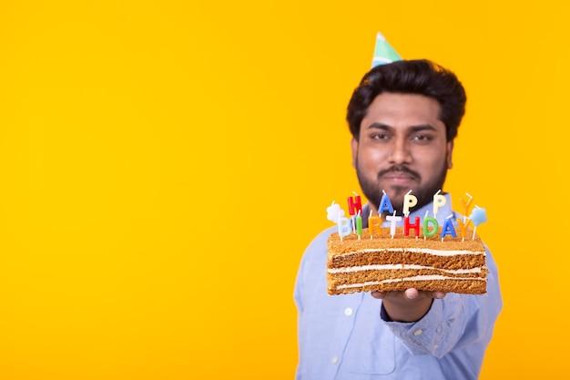 Verrückter fröhlicher junger indischer mann im papierglückwunschhut, der kuchen alles gute zum geburtstag stehend hält