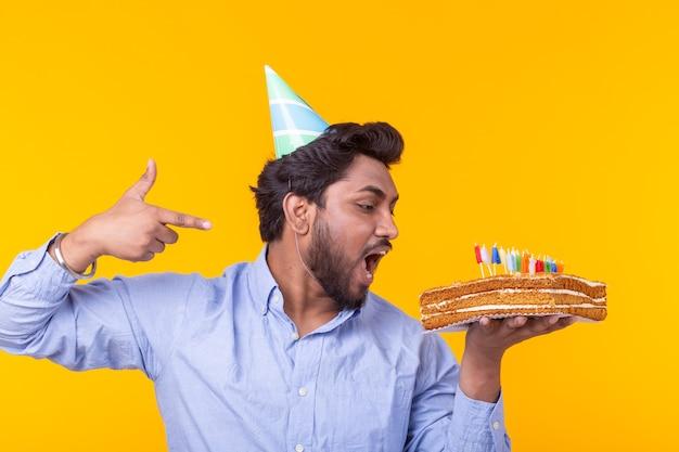 Verrückter fröhlicher junger indischer mann im papierglückwunschhut, der kuchen alles gute zum geburtstag steht, der auf einer gelben oberfläche steht. jubiläums-glückwunschkonzept.