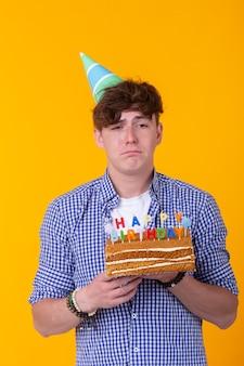 Verrückter fröhlicher junger mann im papierglückwunschhut, der kuchen alles gute zum geburtstag hält, der auf einem steht