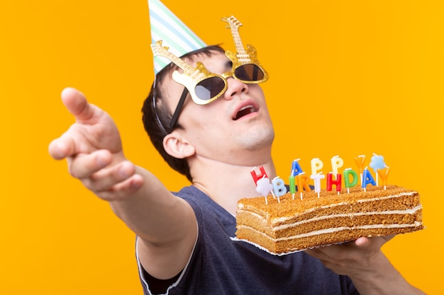 Verrückter fröhlicher junger mann in den gläsern und im papierglückwunschhüten, die kuchen alles gute zum geburtstag halten