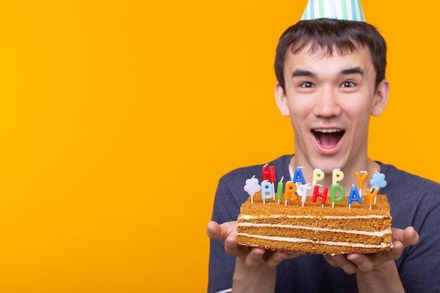 Verrückter fröhlicher junger mann in gläsern und papierglückwunschhüten, die kuchen alles gute zum geburtstag halten
