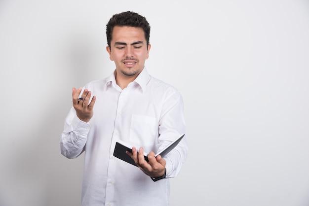 Verrückter geschäftsmann, der notizbuch auf weißem hintergrund liest.