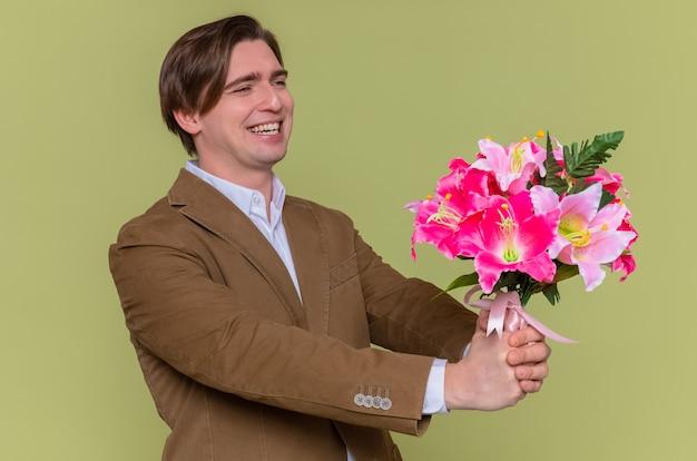 Verrückter glücklicher junger mann, der blumenstrauß hält, der beiseite schaut und fröhlich lächelt, um mit internationalem frauentag zu gratulieren, der über grüner wand steht