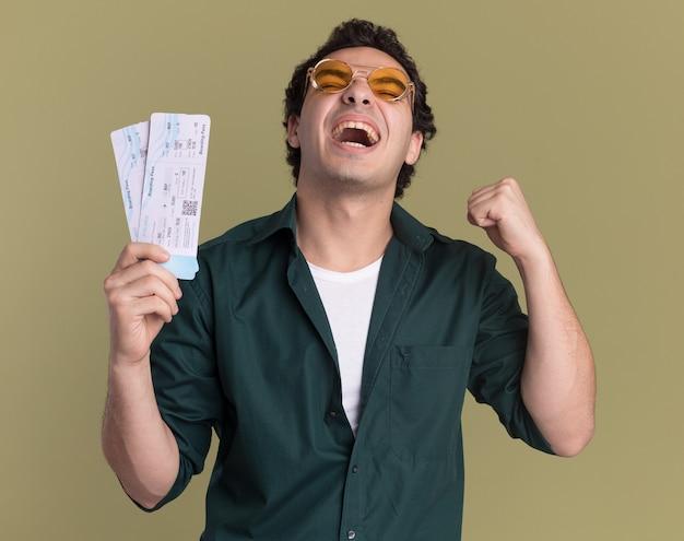 Verrückter glücklicher junger mann im grünen hemd, das brillen hält, die flugtickets halten, die faust ballen, die seinen erfolg erfreut, der über grüner wand steht