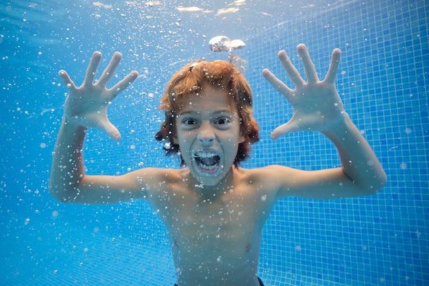 Verrückter junge, der unter wasser des swimmingpools grimasse macht