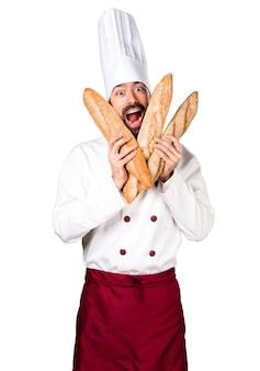 Verrückter junger bäcker, der etwas brot hält
