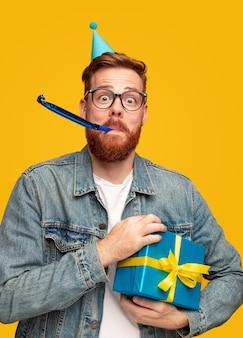 Verrückter junger mann mit ingwerbart, der verpackte geschenkbox hält und krachmacher während der geburtstagsfeier gegen gelben hintergrund bläst