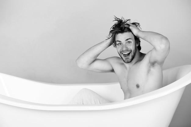 Verrückter junger mann mit muskulösem körper, der in der badewanne sitzt. kerl in der badewanne. spa und schönheit, entspannung und hygiene, gesundheitswesen, kopierraum. schwarz-weiss.