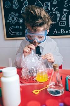 Verrückter kleiner junge wissenschaftler mit brille und schmutzigem gesicht macht seifenblasen mit strohhalm in glas