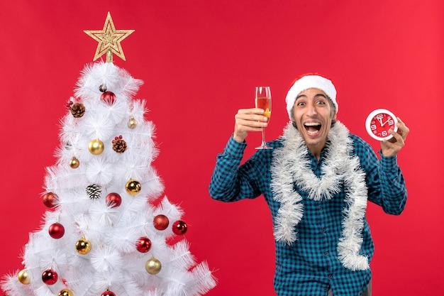 Verrückter lustiger junger mann mit weihnachtsmannhut und erhöhen eines glases wein und uhr nahe weihnachtsbaum auf rot