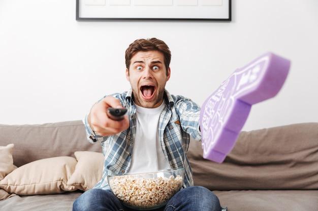 Verrückter männlicher fußballfan, der schreit, während er fernsieht und fernbedienung auf kamera mit großem spielzeughandschuh zur hand und schüssel popcorn zeigt