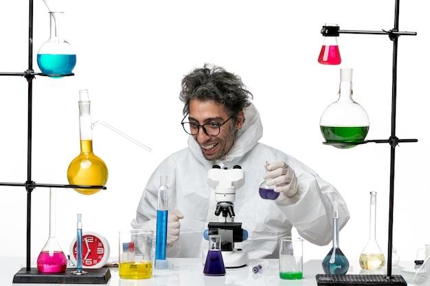 Verrückter männlicher wissenschaftler der vorderansicht im speziellen schutzanzug, der um tisch mit lösungen auf covid lab science virus des weißen hintergrundkrankheitssitzes sitzt