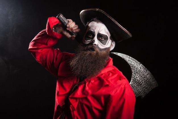 Verrückter mann verkleidet wie ein mittelalterlicher pirat mit langem bart und seiner axt für halloween auf schwarzem hintergrund.