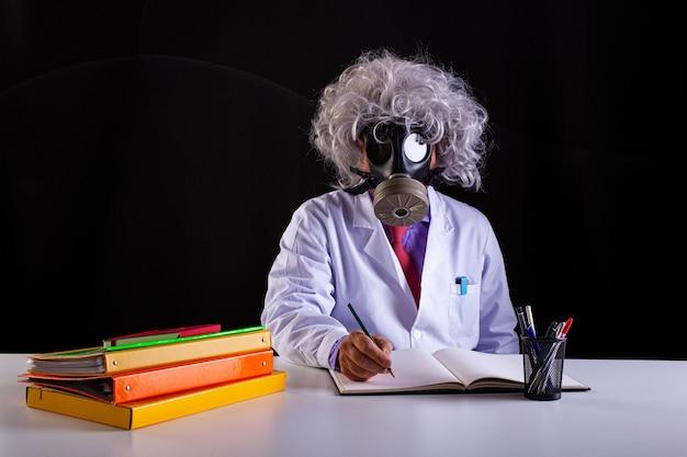 Verrückter naturwissenschaftslehrer im weißen kittel mit ungepflegtem haar sitzt am schreibtisch und trägt eine gasmaske
