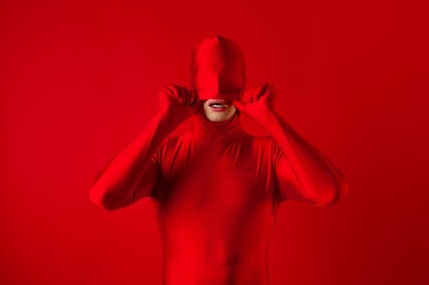 Verrückter roter mann auf einer roten wandfigur in einem trikot, das den ganzen körper bedeckt