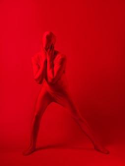 Verrückter roter mann auf rotem hintergrund figur in einem trikot, das den ganzen körper bedeckt covering