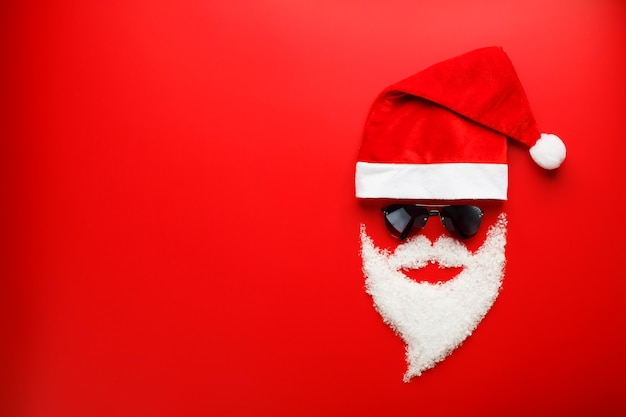Verrückter santa claus hat und bart gemacht vom schnee mit schwarzen gläsern