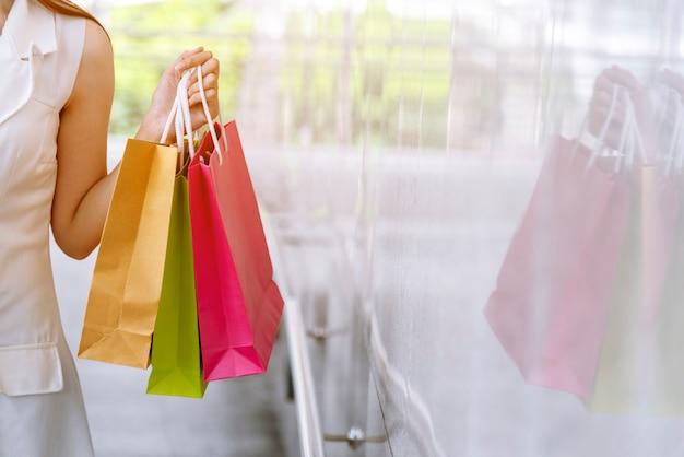 Verrückter shopaholic der frauen, der einkaufstaschen, geld, kreditkartenperson an einkaufszentren hält.