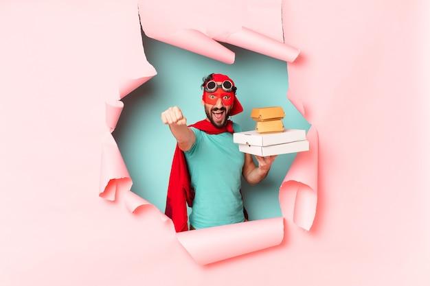 Verrückter superhelden-mann. glücklicher und überraschter ausdruck. take-away-fast-food-konzept