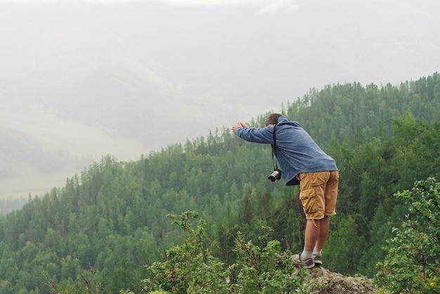 Verrückter tourist auf berggipfel. freudiger reisender taucht unter regen in den abgrund. verrückter mann springt auf felsigen gipfel.