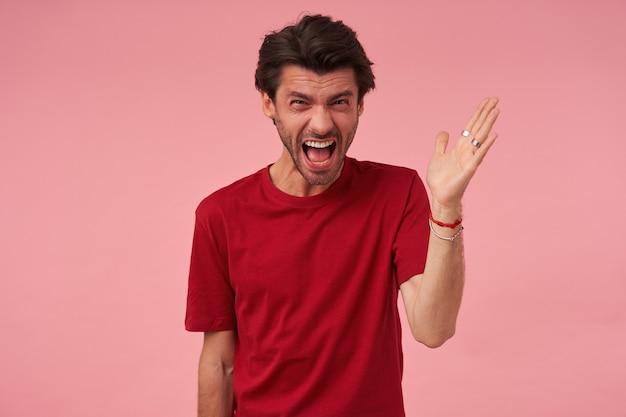 Verrückter verrückter junger mann mit borsten im roten t-shirt fühlt sich gereizt und schreit