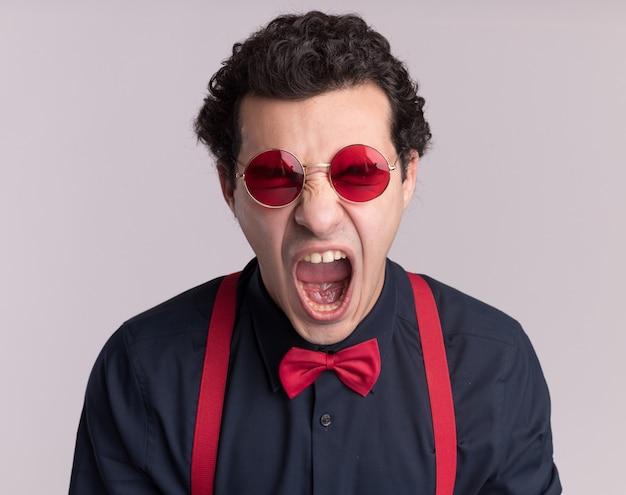 Verrückter verrückter stilvoller mann mit fliege, die brille und hosenträger trägt, die mit aggressivem ausdruck schreien, der über weißer wand steht
