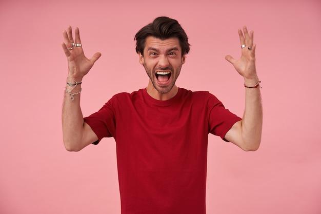 Verrückter wütender junger mann mit borsten und erhobenen händen im roten t-shirt, das kamera betrachtet und schreit