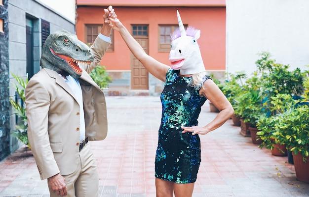 Verrücktes älteres paar, das um stadtstraße tanzt und t-rex und hühnermaske trägt