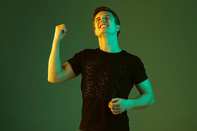 Verrücktes glück, feiert sieg. porträt des kaukasischen mannes lokalisiert auf grünem studiohintergrund im neonlicht. schönes männliches modell im schwarzen hemd. konzept der menschlichen emotionen, gesichtsausdruck, verkauf, anzeige.