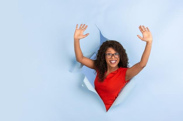 Verrücktes glückliches zeigen fröhliche afroamerikanische junge frau in zerrissenem gelbem papier