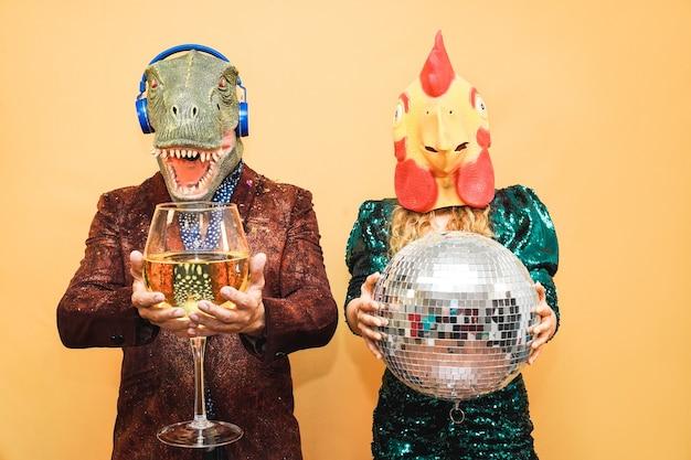 Verrücktes junges paar, das spaß für silvesterparty mit t-rex und hühnermaske hat - mode-leute, die auf festveranstaltung feiern - feiertagskonzept - fokus auf gesichter