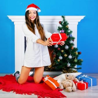 Verrücktes lächelndes mädchen, das weihnachtsgeschenke öffnet. sitzen in der nähe von kamin und neujahr geschmückten baum. positive emotionen und glück.