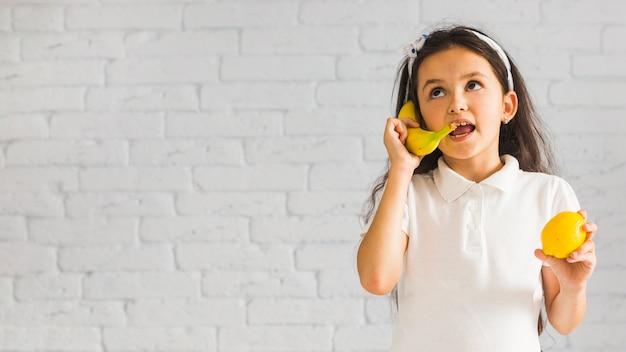Verrücktes mädchen, das zitrone in ihrer hand macht spaß mit gelber banane hält
